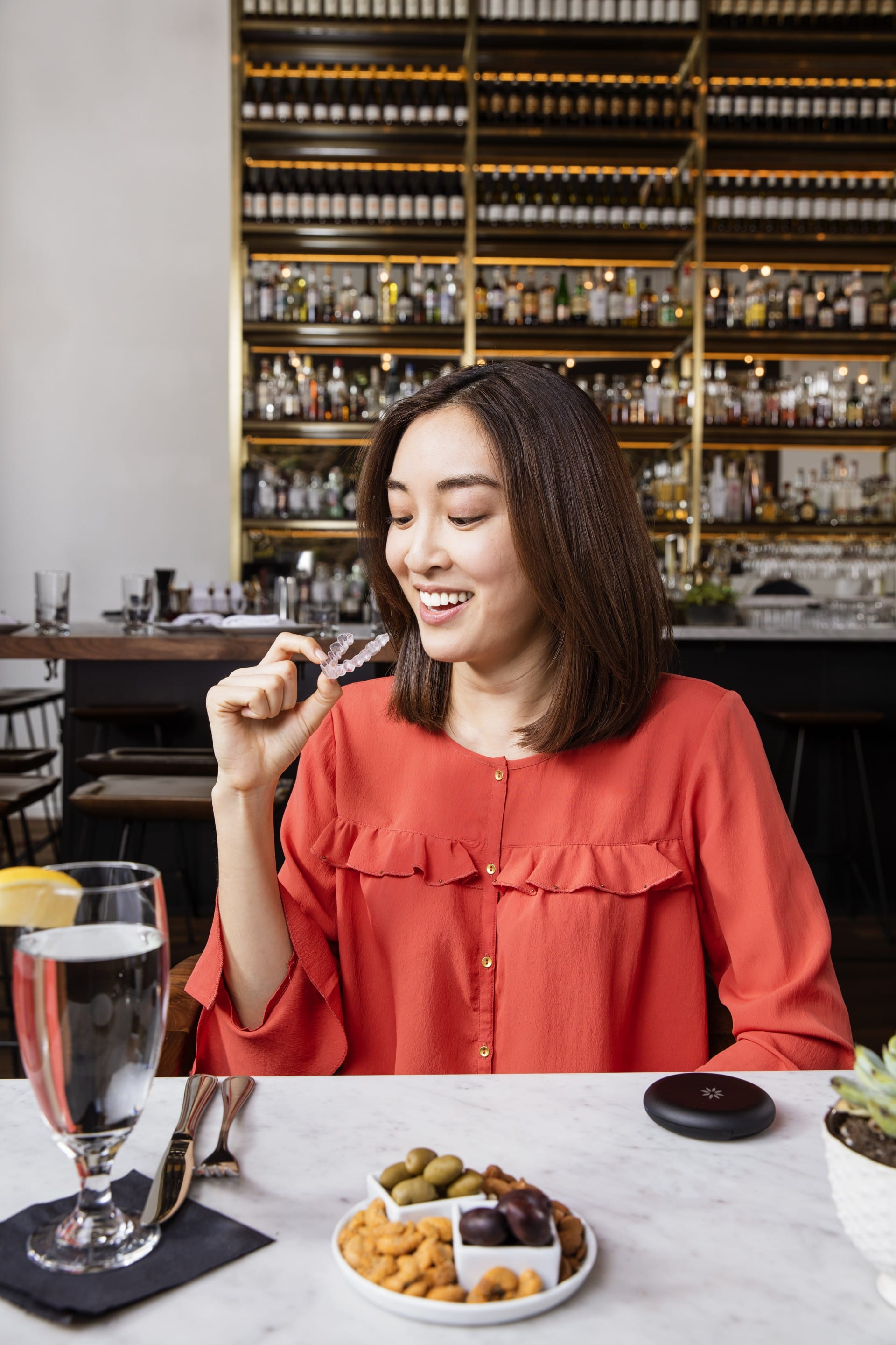 Smiling woman removing her Invisalign® clear aligner before eating at a restaurant