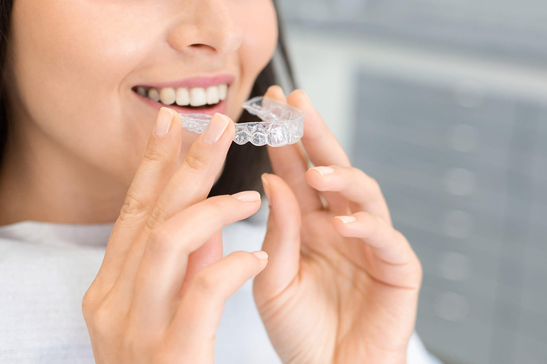 Woman in inserts an Invisalign clear orthodontic aligner from best dentist East Sacramento CA