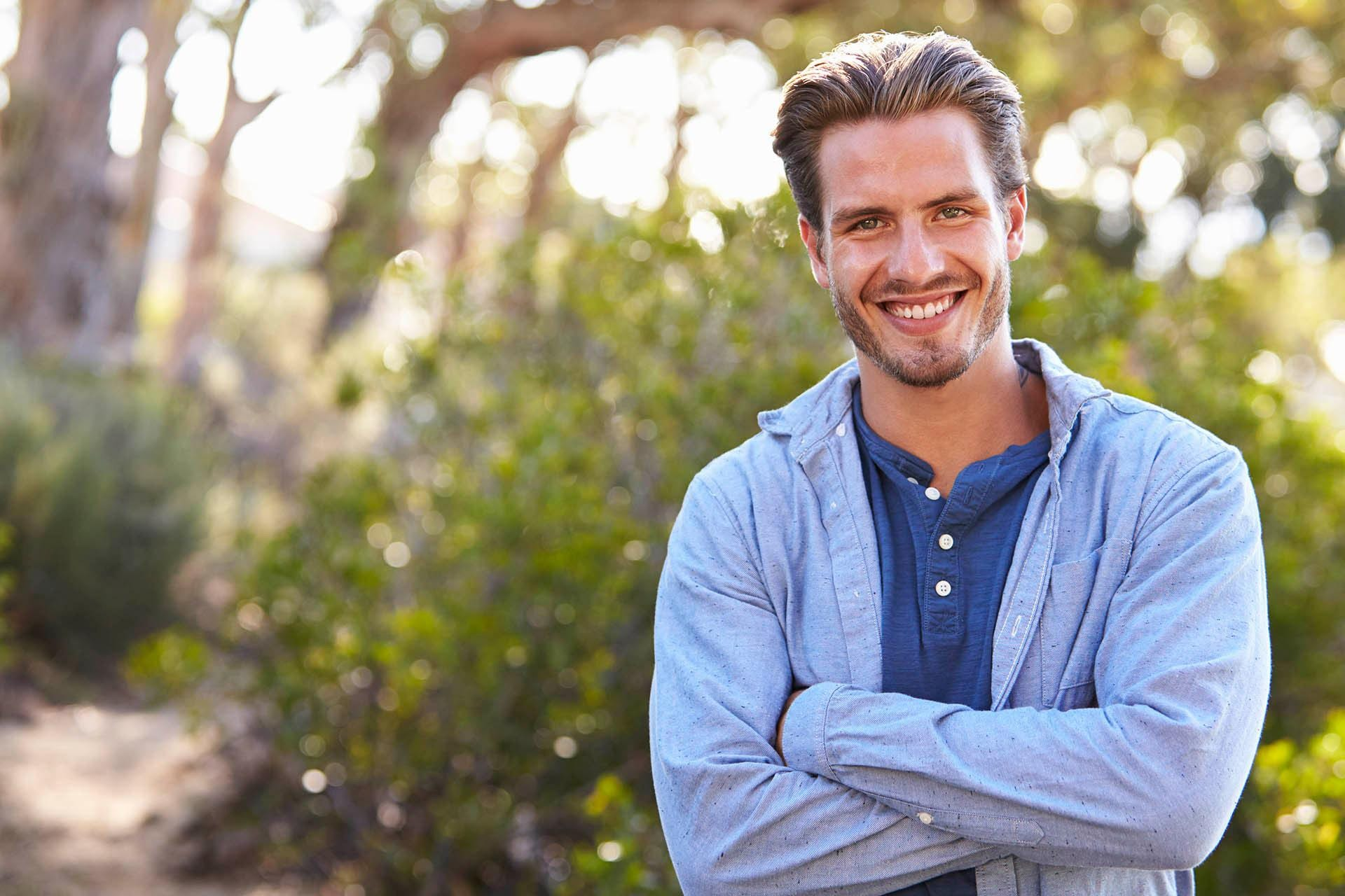 Man outdoors shows off his smile from the best dentist Rancho Cordova, CA