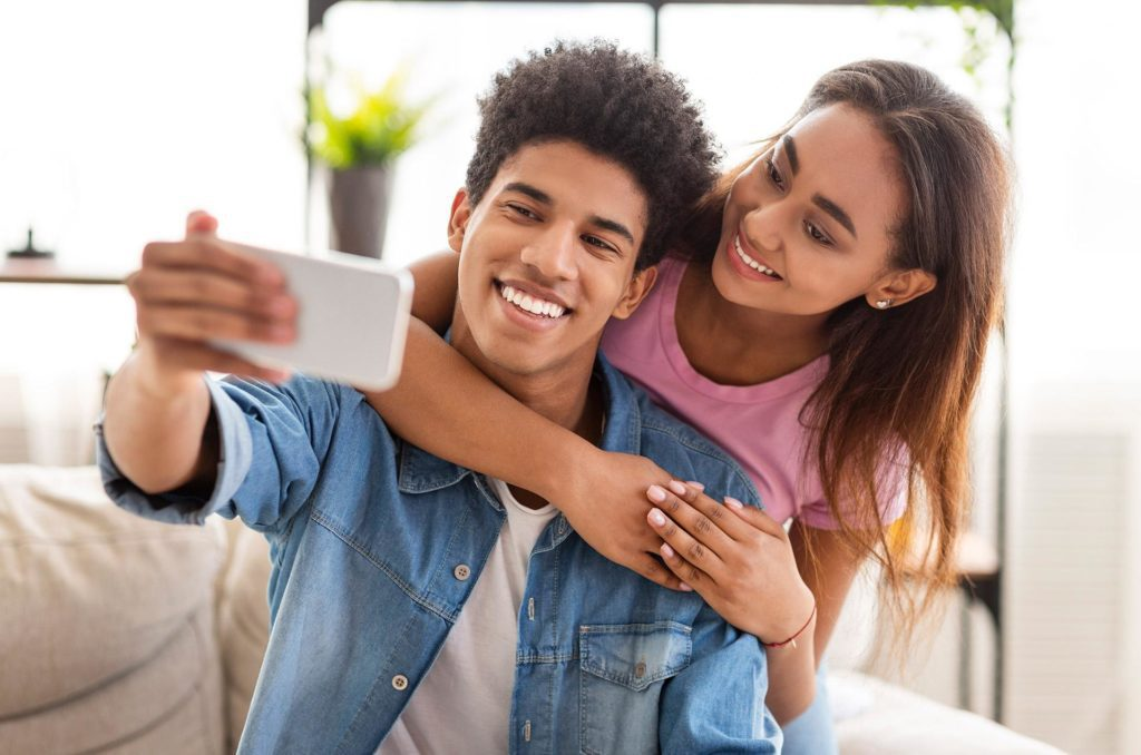 Happy young couple in Carmichael CA shows off their beautiful smiles for a selfie
